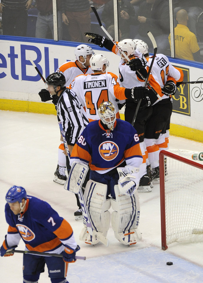 Photo - Philadelphia Flyers' Vincent Lecavalier (40), second from left, background, celebrates his second goal in the first period with teammates as New York Islanders'  Matt Carkner (7) and goalie Kevin Poulin (60) react in an NHL hockey game at the Nassau Coliseum on Saturday, Oct. 26, 2013, in Uniondale, N.Y. (AP Photo/Kathy Kmonicek)