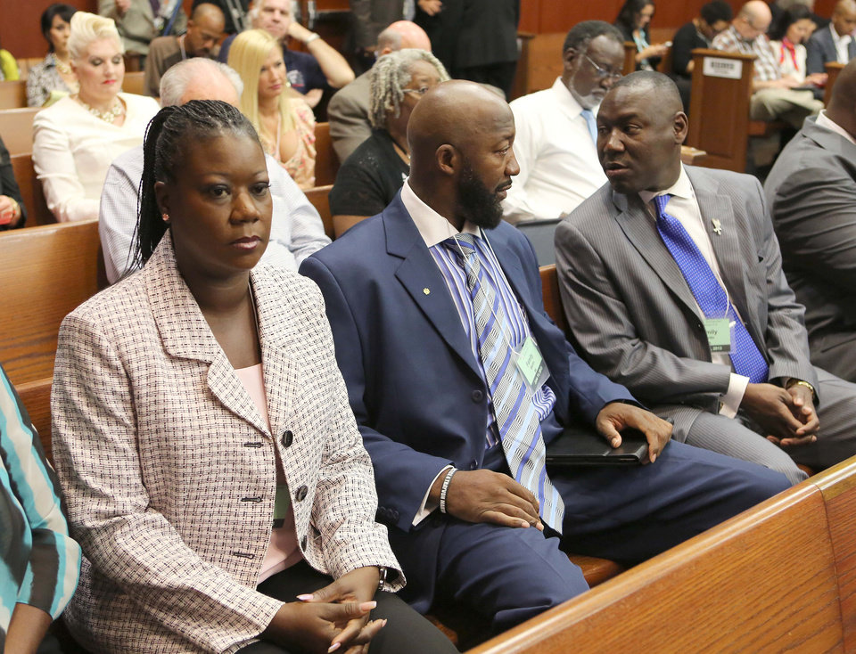 Photo - Tracy Martin, center, and Sybrina Fulton, left, parents of slain teen Trayvon Martin, listen to their attorney Benjamin Crump, right, in Seminole circuit court during George Zimmerman's trial, in Sanford, Fla., Tuesday, June 11, 2013. Zimmerman has been charged with second-degree murder for the 2012 shooting death of Trayvon Martin.(AP Photo/Orlando Sentinel, Joe Burbank, Pool)