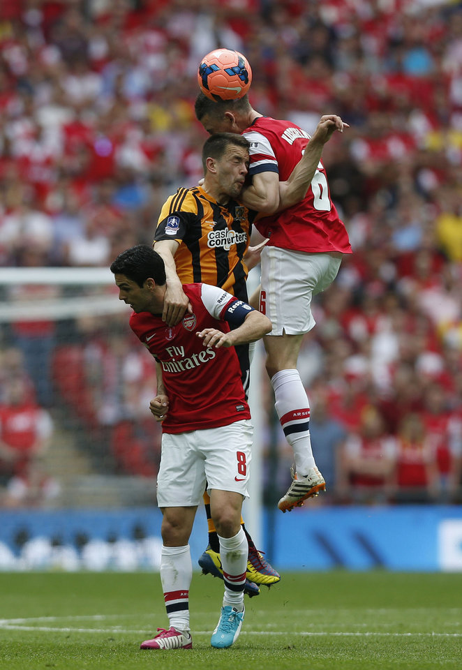 Photo - Arsenal's Laurent Koscielny, right, and Mikel Arteta, left, competes for the ball with Hull City's Matt Fryatt during their English FA Cup final soccer match at Wembley Stadium in London, Saturday, May 17, 2014. (AP Photo/Sang Tan)