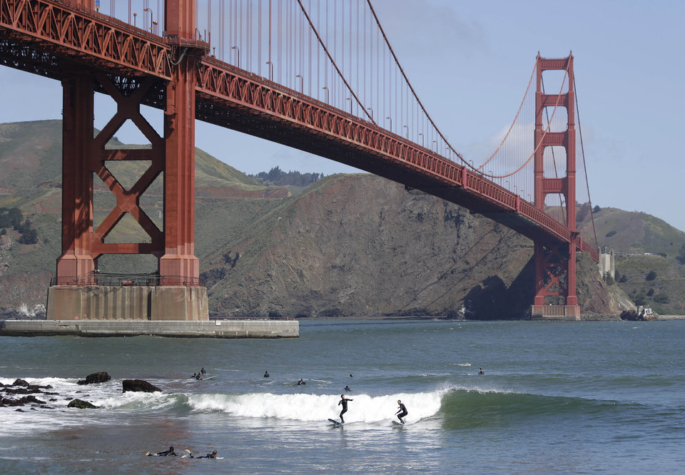 Photo - FILE - Two surfers ride a wave near Fort Point below the Golden Gate Bridge in this May 3, 2014 file photo in San Francisco. The bridge's board is set to vote Friday June 27, 2014 on a $76 million funding package for a net. If approved, it would be a major step in a decades-long debate pitting the families of suicide victims and other supporters of a suicide barrier versus those who believe it will not prevent people from finding other ways to take their lives on the span. (AP Photo/Eric Risberg, File)