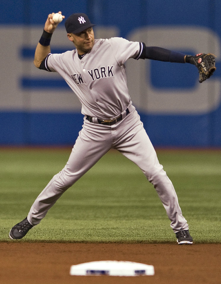 Photo - New York Yankees shortstop Derek Jeter throws to first after fielding a ground ball hit by Tampa Bay Rays' Matt Joyce during the first inning of a baseball game Friday, April 18, 2014, in St. Petersburg, Fla. Joyce was out. (AP Photo/Steve Nesius)