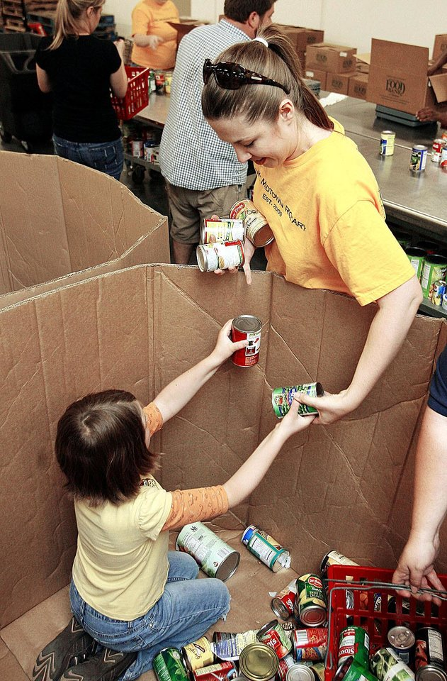 Photo - Sheri Guyse and her daughter, Gabi, 8,  volunteer  June 6 at the Regional Food Bank in Oklahoma City.  BY PAUL HELLSTERN, THE OKLAHOMAN