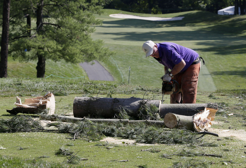 Photo -   A worker chainsaws a tree that fell onto a tee box on the the 12th hole at Congressional Country Club in Bethesda, Md., Saturday, June 30, 2012, after a strong storm blew through overnight. The AT&T National golf tournament was postponed to allow workers to clear the course. (AP Photo/Patrick Semansky)