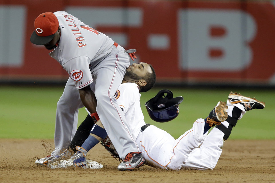 Photo - Cincinnati Reds second baseman Brandon Phillips, left, reaches back to tag out Houston Astros' Jonathan Villar as he tries to stretch a single in the first inning of a baseball game Tuesday, Sept. 17, 2013, in Houston. (AP Photo/Pat Sullivan)
