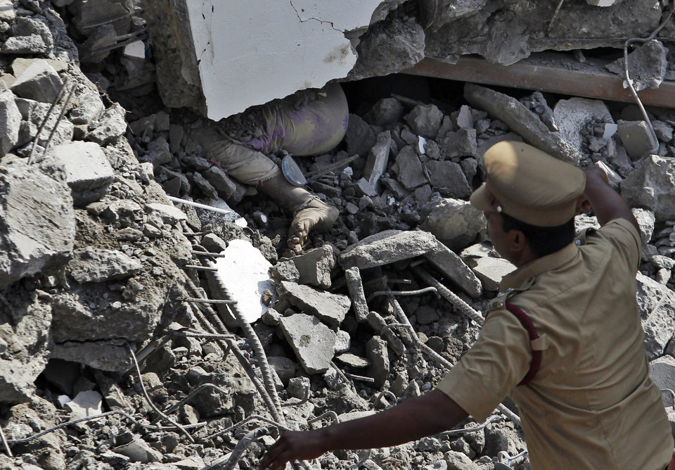 Photo - The body of a woman worker lies beneath piles of concrete in the rubble of a building that collapsed late Saturday during monsoon rains on the outskirts of Chennai, India, Sunday, June 29, 2014. Police said dozens of workers have been pulled out so far and the search is continuing. (AP Photo/Arun Sankar K)