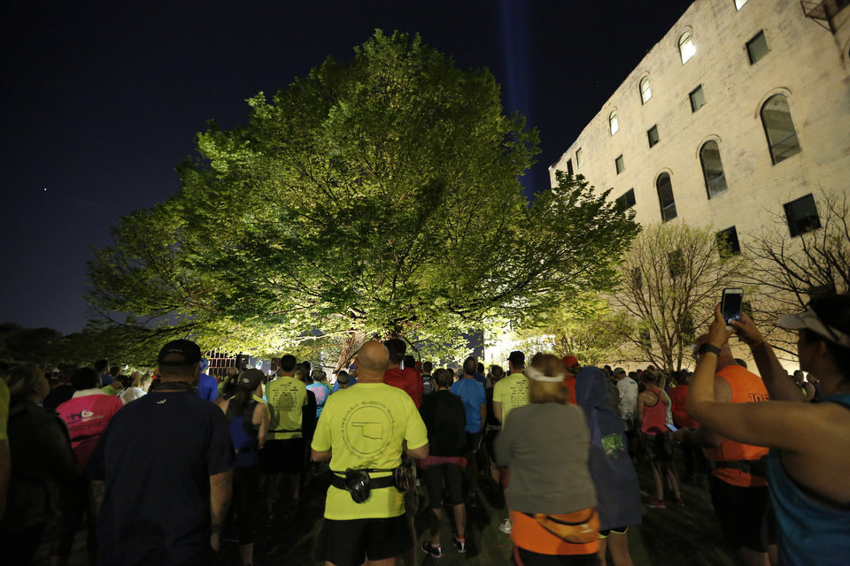 Photo - People pray at the Survivor Tree before the Oklahoma City Marathon in Oklahoma City,  Sunday, April 29, 2018. Photo by Sarah Phipps, The Oklahoman