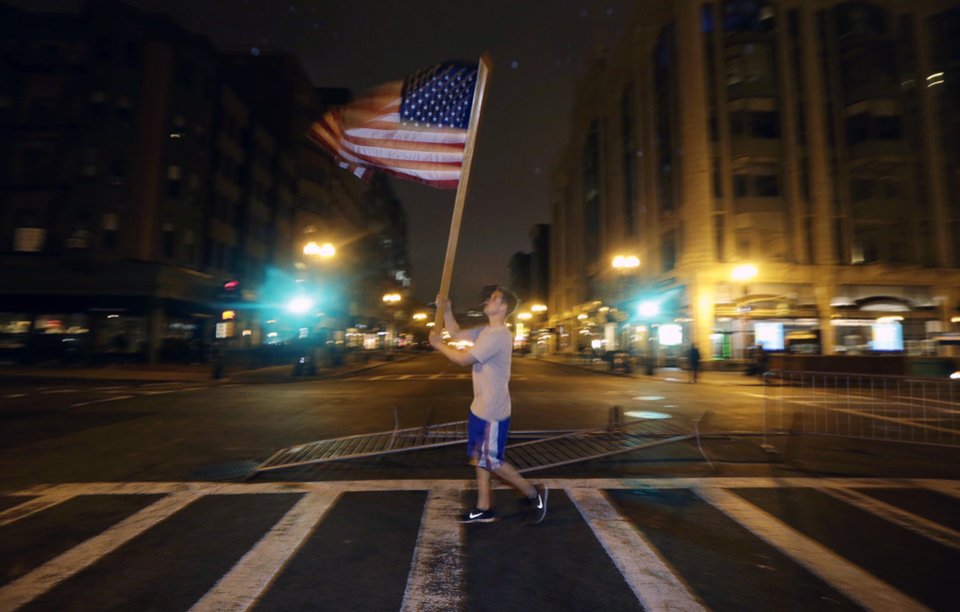 Photo - Joseph Eli Libby, 20, of Boston, carries a flag near a makeshift memorial on Boylston Street, near the finish line of the Boston Marathon, Friday, April 19, 2013, in Boston. Boston Marathon bombing suspect Dzhokhar Tsarnaev was captured in Watertown, Mass. The 19-year-old college student wanted in the bombings was taken into custody Friday evening after a manhunt that left the city virtually paralyzed and his older brother and accomplice dead. (AP Photo/Julio Cortez)