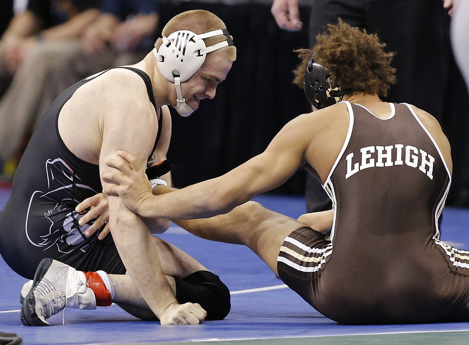 Photo - Oklahoma State's Chris Perry takes on Lehigh' s Elliot Riddick in the 174 pound match during the 2014 NCAA Div. 1 Wrestling Championships at Chesapeake Energy Arena in Oklahoma City, Okla. on Friday, March 21, 2014. Photo by Chris Landsberger, The Oklahoman