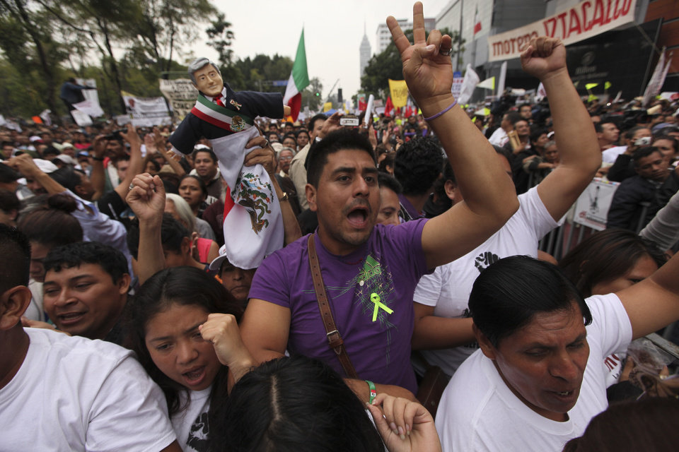 Photo - Supporters of former presidential candidate Andres Manuel Lopez Obrador cheer as they listen to Lopez Obrador during an act to protest against the government's proposed energy reforms that would allow private companies to explore the country's oil and gas reserves, in Mexico City, Sunday Sept. 8, 2013. The proposed reform requires constitutional changes that strike at the heart of one of Mexico's proudest moments: President Lazaro Cardenas' nationalization of the oil company in 1938. (AP Photo/Marco Ugarte)