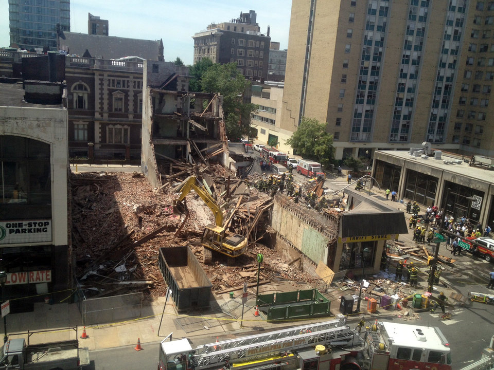 Photo - Emergency personnel respond to a building collapse in downtown Philadelphia, where the city fire commissioner says as many as eight to 10 people are believed trapped in the rubble, Wednesday, June 5, 2013. (AP Photo/Dino Hazell)
