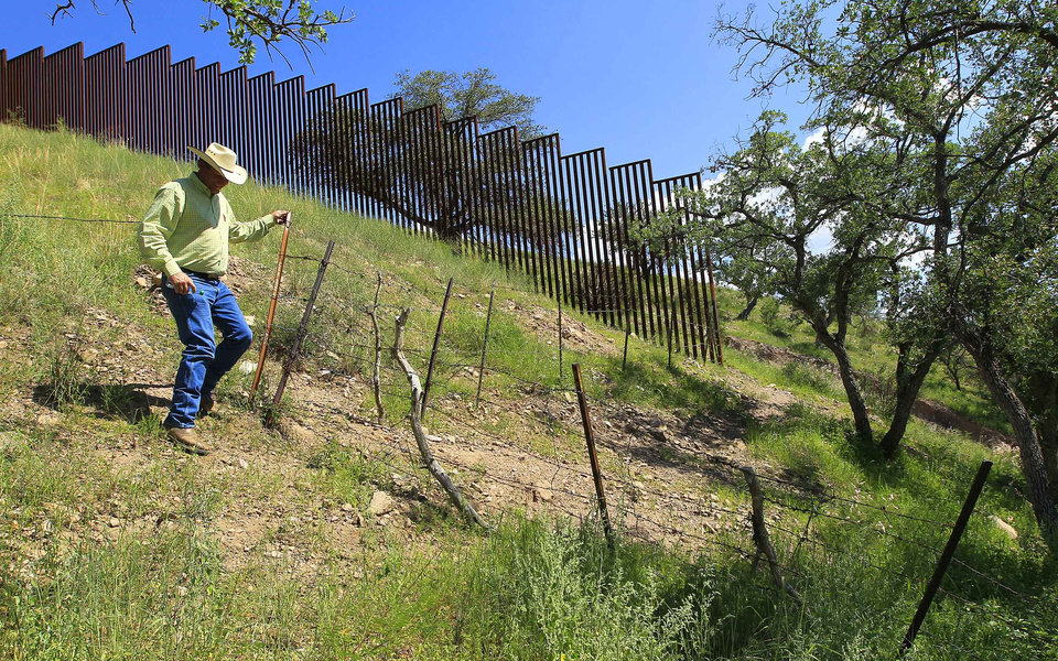 In this Friday, Aug. 10, 2012 photo, rancher Dan Bell, who leases a 35,000-acre cattle ranch along the border between the United States and Mexico, checks out part of the property where the barbed-wire fence is often damaged by illegal border crossers, in Nogales, Ariz. When Bell drives through the property, he speaks of the hurdles that the Border Patrol faces in his rolling green hills of oak and mesquite trees: The hours it takes to drive to some places, the wilderness areas that are generally off-limits to motorized vehicles, and the environmental reviews required to extend a dirt road. (AP Photo/Ross D. Franklin)