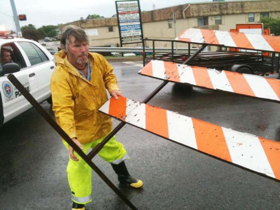 Photo - Workers put up a barricade on Hefner Rd because of flooding. Photo by John Clanton, The Oklahoman