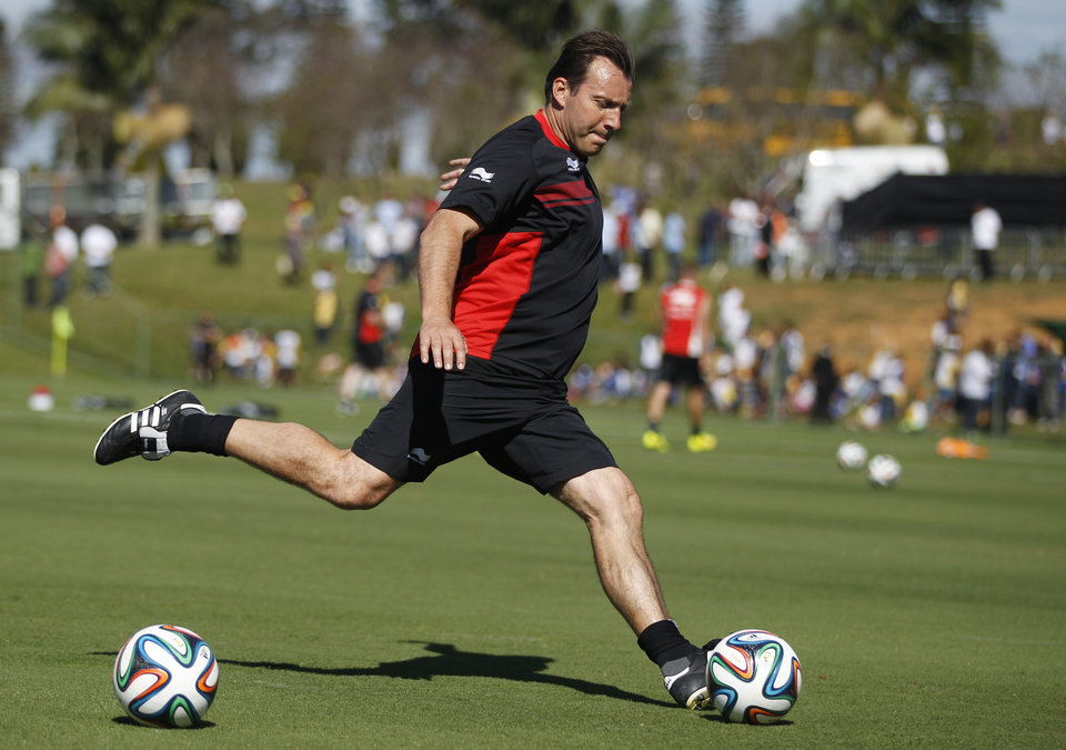 Photo - Belgium's head coach Marc Wilmots kicks a ball during a team training session in Mogi Das Cruzes, Brazil, Friday, June 13, 2014. Belgium plays in group H of the 2014 soccer World Cup. (AP Photo/Andrew Medichni)