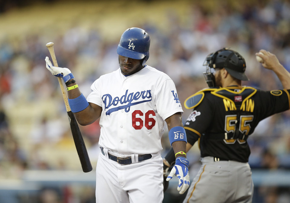 Photo - Los Angeles Dodgers' Yasiel Puig, left, heads toward the dugout after he struck out as Pittsburgh Pirates catcher Russell Martin throws the ball to starting pitcher Francisco Liriano during the first inning of a baseball game Friday, May 30, 2014, in Los Angeles. (AP Photo/Jae C. Hong)