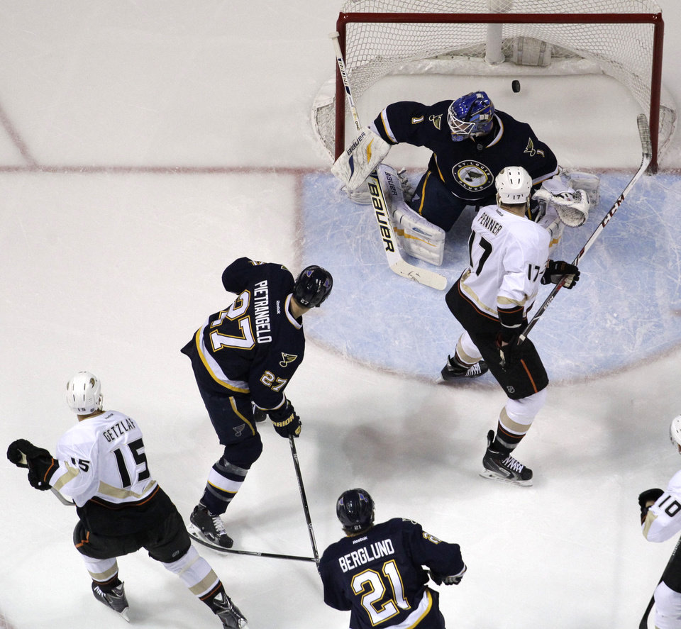Photo - Anaheim Ducks' Ryan Getzlaf (15) watches as his shot slips past St. Louis Blues goalie Brian Elliott for a goal during the first period of an NHL hockey game on Saturday, Jan. 18, 2014, in St. Louis. Ducks' Dustin Penner (17), Blues' Alex Pietrangelo (27) and Blues' Patrik Berglund (21), of Sweden, watch the play. (AP Photo/Jeff Roberson)