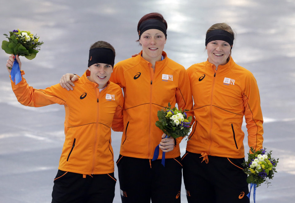 Photo - Athletes from the Netherlands, from left to right, silver medallist Ireen Wust, Gold medallist Jorien ter Mors and bronze medallist Lotte van Beek celebrate during the flower ceremony for the women's 1,500-meter speedskating race at the Adler Arena Skating Center during the 2014 Winter Olympics in Sochi, Russia, Sunday, Feb. 16, 2014. (AP Photo/Matt Dunham)