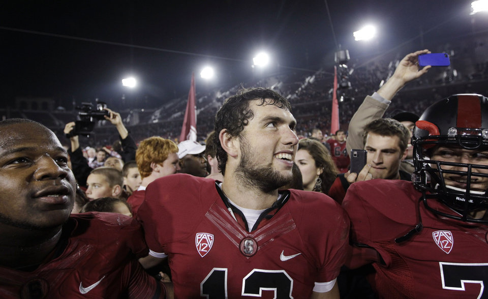 Stanford quarterback Andrew Luck, center, smiles with teammates after Stanford defeated Notre Dame 28-14 in an NCAA college football game in Stanford, Calif., Saturday, Nov. 26, 2011. (AP Photo/Paul Sakuma) ORG XMIT: CAPS121