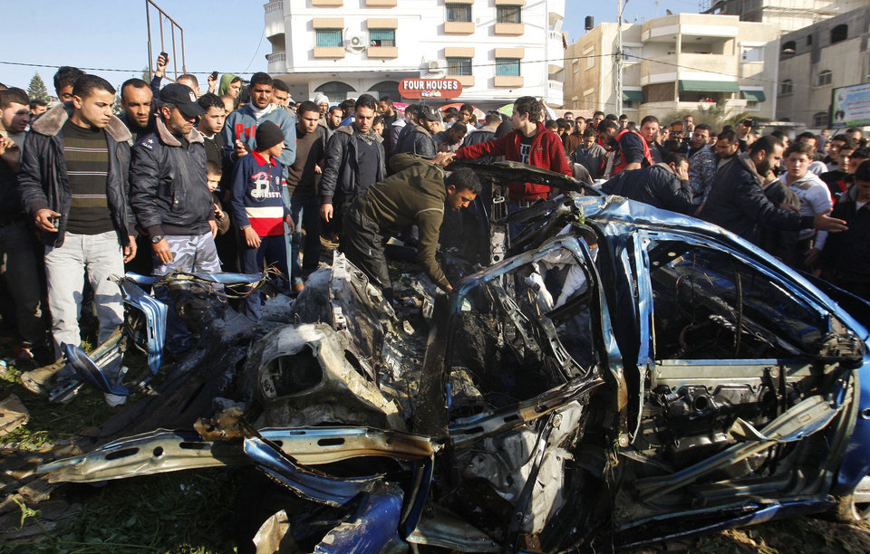 Palestinians gather around the wreckage of a car targeted in an airstrike in Gaza City, Friday, March 9, 2012. An Israeli airstrike killed top Palestinian militant commander Zuhair al-Qaissi and a second militant in Gaza on Friday in the highest profile attack against the coastal strip in months. (AP photo/Hatem Moussa) ORG XMIT: DV108