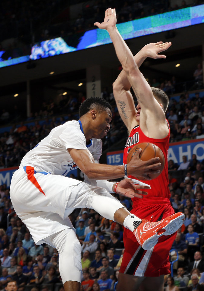 Photo - Oklahoma City's Russell Westbrook (0) passes around Portland's Meyers Leonard (11) during an NBA basketball game between the Oklahoma City Thunder and the Portland Trailblazers at the Chesapeake Energy Arena in Oklahoma City, Monday, March 14, 2016. Photo by Nate Billings, The Oklahoman