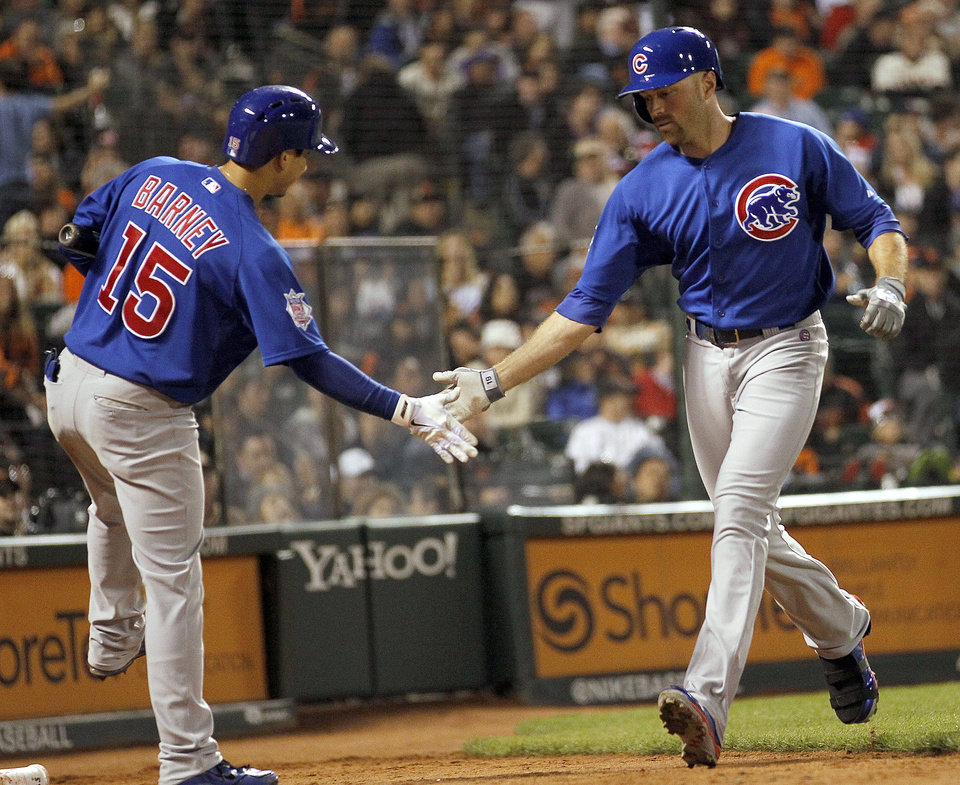 Photo - Chicago Cubs' Nate Schierholtz, right, is congratulated by Darwin Barney after hitting a solo home run against San Francisco Giants relief pitcher Sergio Romo in the ninth inning of a baseball game Saturday, July 27, 2013, in San Francisco. (AP Photo/Tony Avelar)