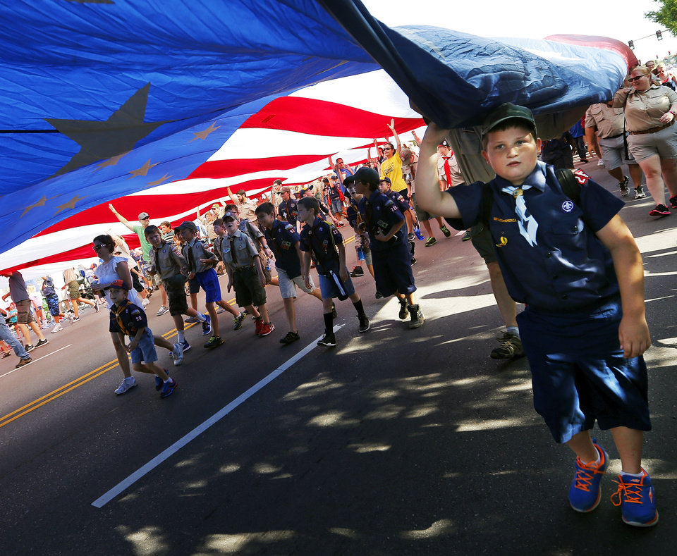 Photo - People involved in scouting carry a giant American flag during the Edmond LibertyFest Parade in downtown Edmond, Okla., on Independence Day, Friday, July 4, 2014. Photo by Nate Billings, The Oklahoman