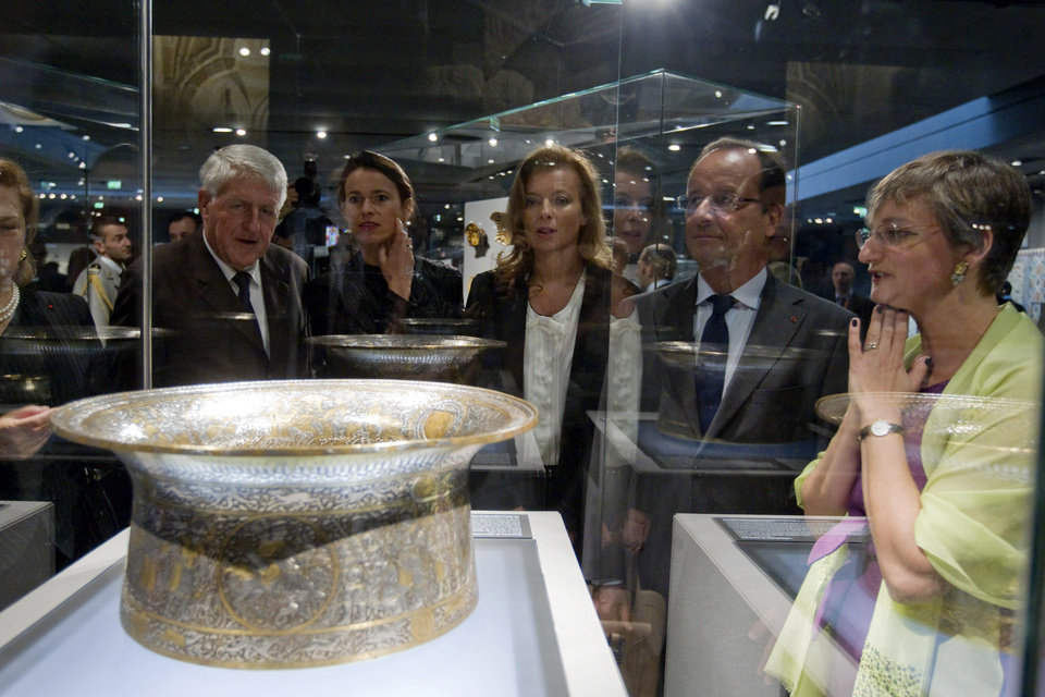 Photo -   French President Francois Hollande, second right, his companion Valerie Trierweiler, center, Culture minister Aurelie Filippetti, second left, and Sophie Makariou, right, chief of Department of Islamic Arts, look at the Saint Louis baptistery, work of Master Muhammad Ibn al-Zain as they visit the new Department of Islamic Arts galleries at the Louvre museum in Paris, Tuesday Sept. 18, 2012. (AP Photo/Gonzalo Fuentes, Pool)