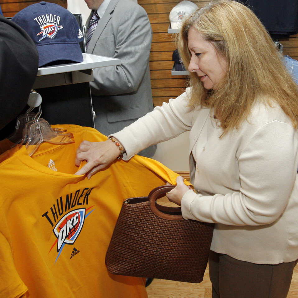 Photo - Kathy Powers looks at a shirt in the OKC Thunder team store after the unveiling of the Oklahoma City Thunder NBA team name at Leadership Square in downtown Oklahoma City, Wednesday, September 3, 2008. NATE BILLINGS, THE OKLAHOMAN