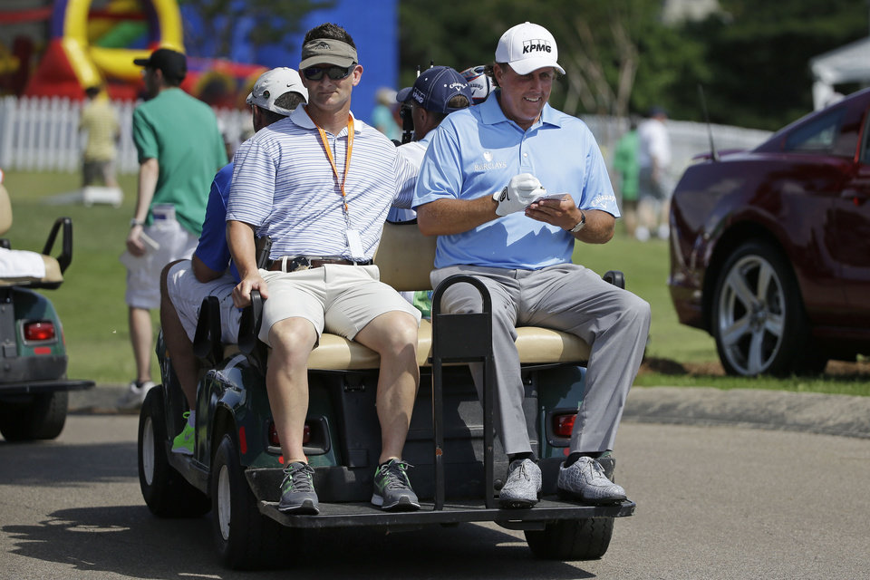 Photo - Phil Mickelson, right, fills out his scorecard as he rides from the 18th green to the first tee during the first round of the St. Jude Classic golf tournament Thursday, June 5, 2014, in Memphis, Tenn. (AP Photo/Mark Humphrey)