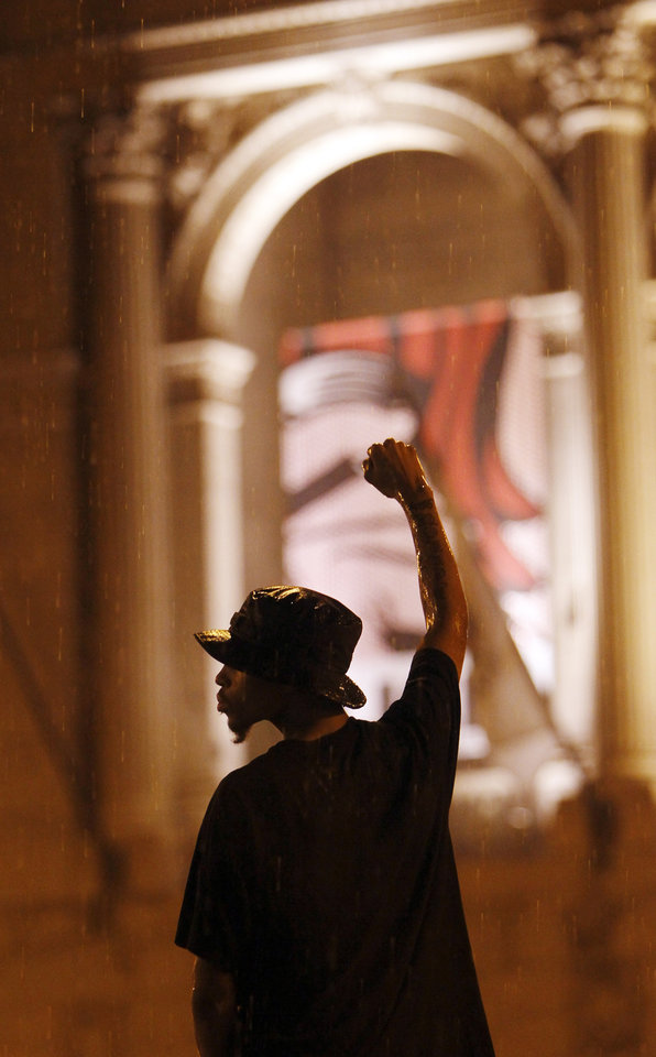 Photo -   A protester gestures in the rain at the Art Institute where First Lady Michelle Obama is hosting a dinner for the spouses of NATO dignitaries during this weekend's summit in Chicago Sunday, May 20, 2012. (AP Photo/Charles Rex Arbogast)