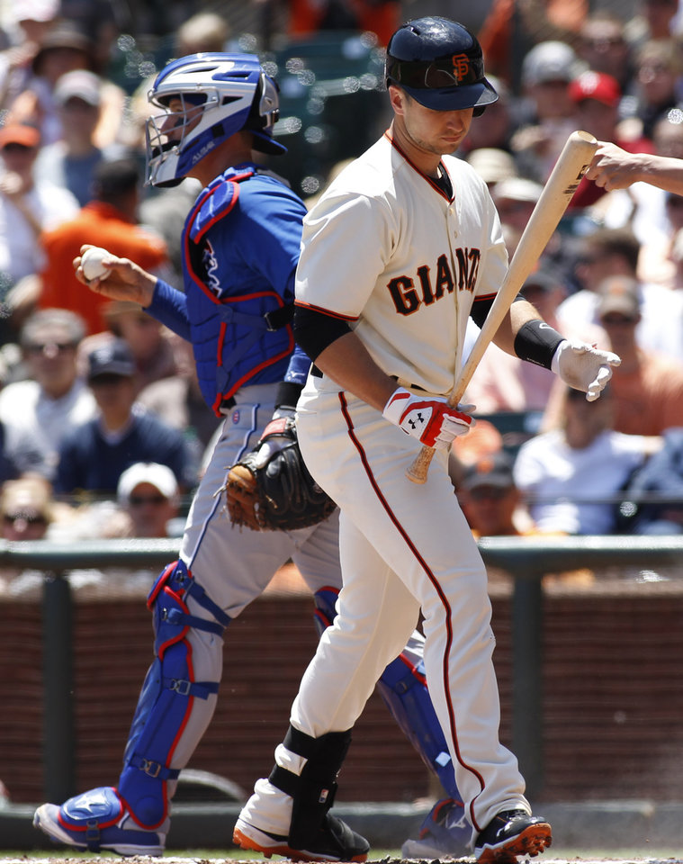 Photo - San Francisco Giants' Buster Posey looks at his bat after striking out, next to Chicago Cubs catcher John Baker during the first inning of a baseball game, Wednesday, May 28, 2014, in San Francisco. (AP Photo/George Nikitin)