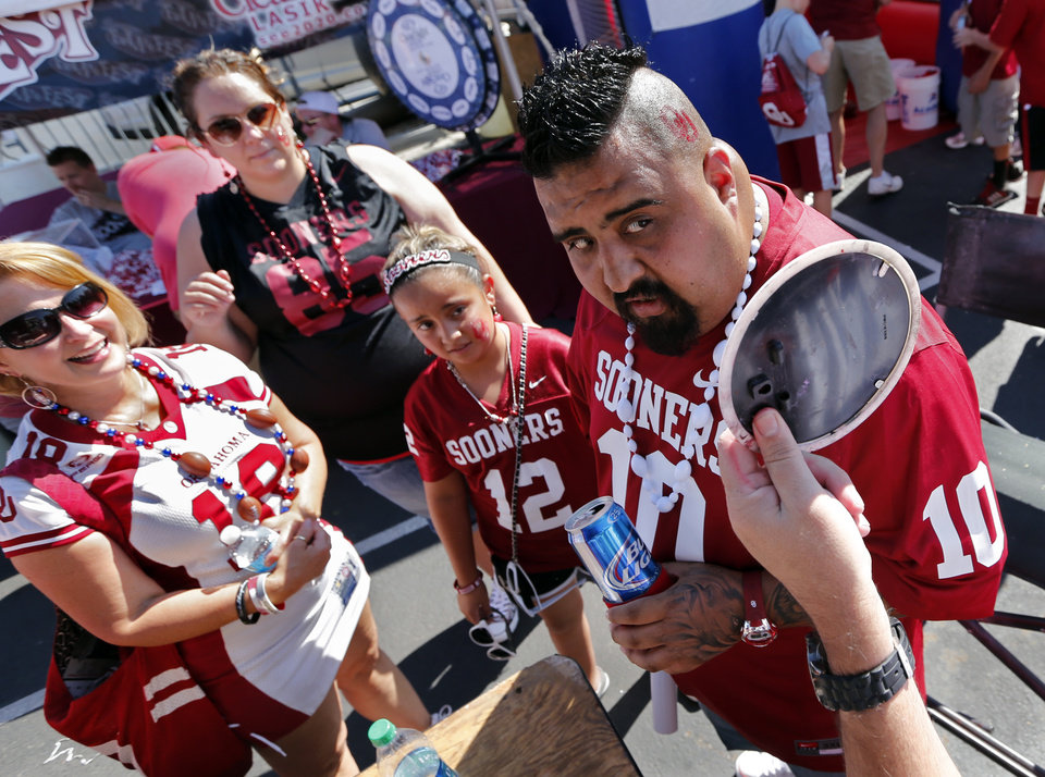 Photo - Leonardo Sanchez gets a red OU painted on his head as Angela Soldan-Cato, left, and Sanchez wife Jessica and daughter Emma look on before a college football game between the University of Oklahoma Sooners (OU) and the Louisiana Tech Bulldogs at Gaylord Family-Oklahoma Memorial Stadium in Norman, Okla., on Saturday, Aug. 30, 2014. Photo by Steve Sisney, The Oklahoman