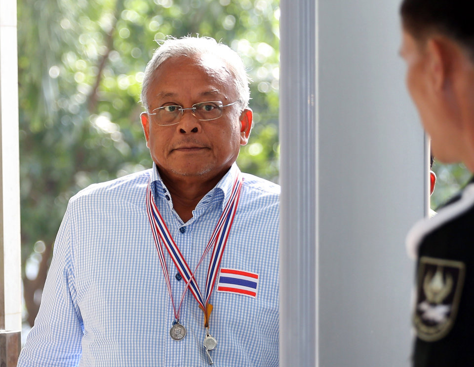Photo - Anti-government protest leader Suthep Thaugsuban, left, arrives at the office of the Attorney General to hear insurrection charge in Bangkok, Thailand Monday, May 26, 2014. Thailand's ruling military council stiffened its warnings Sunday against protests over its takeover of power, with its patience apparently wearing thin over demonstrations that have been growing in size and boldness. (AP Photo/Apichart Weerawong)