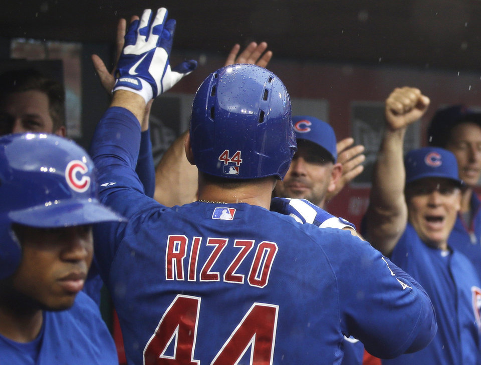 Photo - Chicago Cubs' Anthony Rizzo (44) is congratulated in the dugout after hitting a solo home run off Cincinnati Reds starting pitcher Johnny Cueto in the first inning of a baseball game, Tuesday, Aug. 26, 2014, in Cincinnati. (AP Photo/Al Behrman)