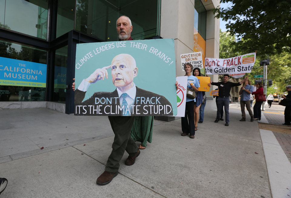 Photo - Richard Gray, left,  joins others in a demonstration calling on Gov. Jerry Brown to end hydraulic fracturing for oil and gas, outside the auditorium  where Brown spoke about climate change at the University of California  Giannini Foundation of Agricultural Economics conference in  Sacramento, Calif., Monday, May 19, 2014.(AP Photo/Rich Pedroncelli)
