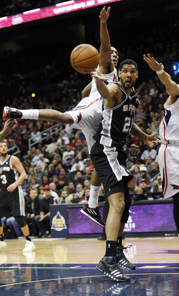 Photo - San Antonio Spurs power forward Tim Duncan (21) passes as Atlanta Hawks point guard Jeff Teague (0) defends in the first half of an NBA  basketball game, Friday, Jan. 24, 2014, in Atlanta.  Teague was injured on the play and left the game. (AP Photo/John Bazemore)