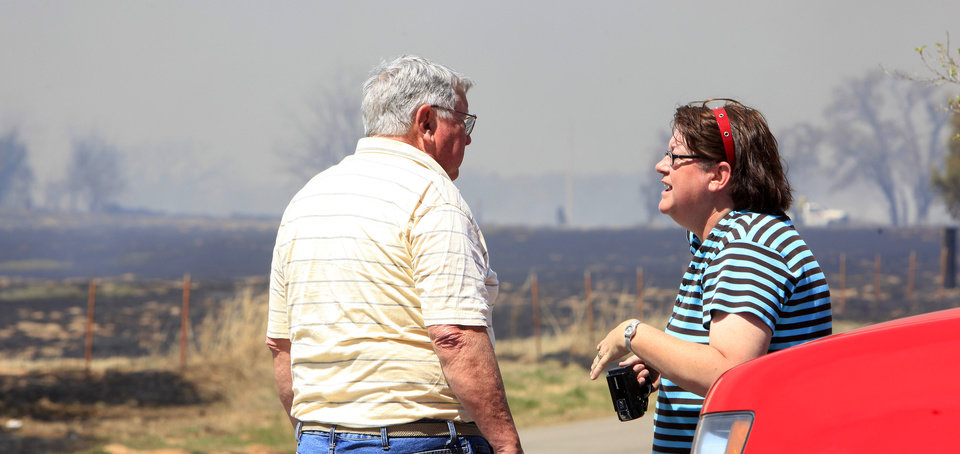 Photo - Fred Anderson, Okla. City, talks with his daughter Rhonda Smith at a command post set up at Wilshire and Post Road as a grass fire burns around both their homes in the background in Oklahoma City Wednesday, April 6, 2011. Photo by Paul B. Southerland, The Oklahoman
