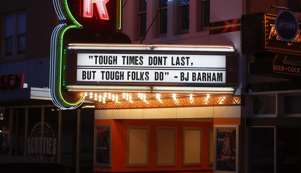 "Photo - The marquee on the closed Tower Theatre displays the lyric ""Tough times don't last, but tough folks do,"" by BJ Barham in the vacant Uptown district along NW 23 between Walker Ave. and Hudson Ave. on what would normally be a busy night for bars and restaurants in Oklahoma City, Thursday, March 26, 2020. [Nate Billings/The Oklahoman]"