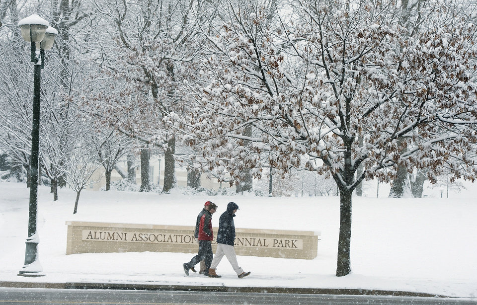 James Madison University students walk along Carrier Drive at the Alumni Association Centennial Park during the snow in Harrisonburg, Va., Sunday evening March 24, 2013. (AP Photo/Daily News-Record, Michael Reilly)