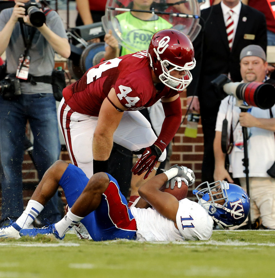 Photo - Jaydan Bird (44) stands over Tre' Parmalee after tackling him during the college football game between the University of Oklahoma Sooners (OU) and the University of Kansas Jayhawks (KU) at Gaylord Family-Oklahoma Memorial Stadium in Norman, Okla., on Saturday, Oct. 20, 2012. Photo by Steve Sisney, The Oklahoman