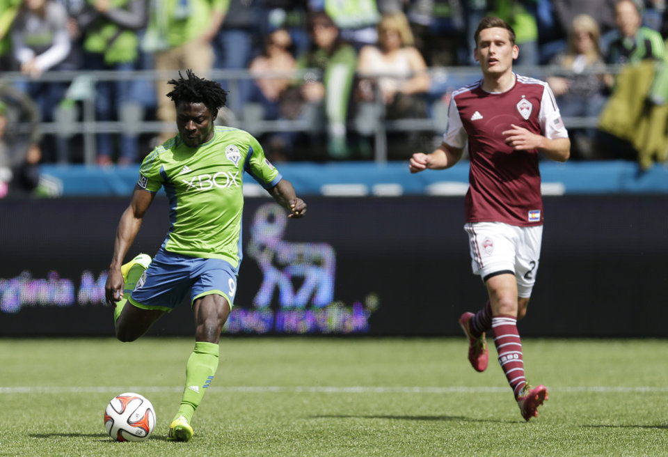 Photo - Seattle Sounders' Obafemi Martins, left, kicks a goal as Colorado Rapids defender Shane O'Neill looks on at right, Saturday, April 26, 2014 in the second half of an MLS soccer match in Seattle. The Sounders defeated the Rapids 4-1. (AP Photo/Ted S. Warren)