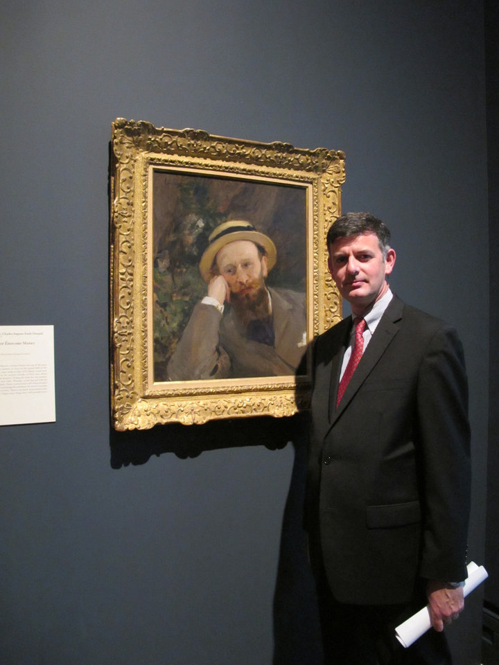 Brian Kennedy, director of the Toledo Museum of Art, poses in front of a portrait of French Impressionist Edouard Manet, Wednesday, Oct. 3, 2012, in Toledo, Ohio. An exhibition of Manet\'s works opened this month and runs through the end of the year before moving onto the Royal Academy of Arts in London. (AP Photo/John Seewer)