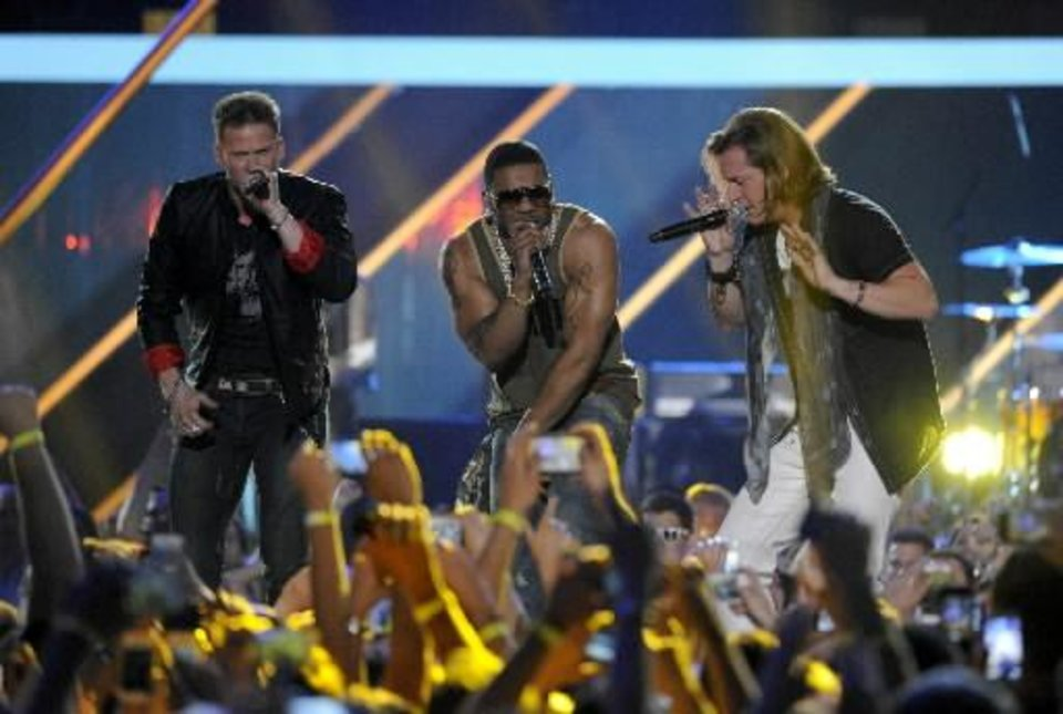 Brian Kelley, left, and Tyler Hubbard, right, of musical group Florida Georgia Line, and Nelly perform at the 2013 CMT Music Awards at Bridgestone Arena on Wednesday, June 5, 2013, in Nashville, Tenn. (AP)