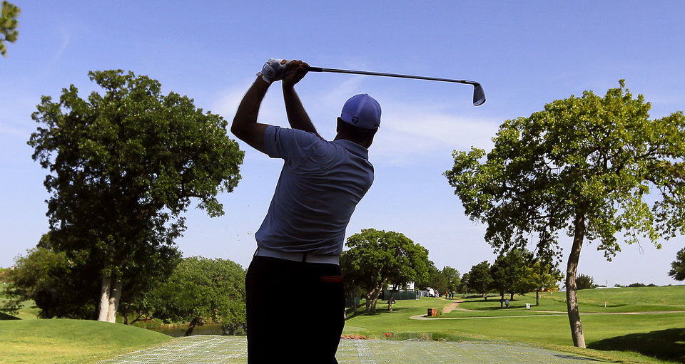 Photo - J.C. Anderson tees off on the thirteenth hole during practice rounds for the U.S. Senior Open golf tournament at Oak Tree National in Edmond, Okla. on Tuesday, July 8, 2014. Photo by Chris Landsberger, The Oklahoman