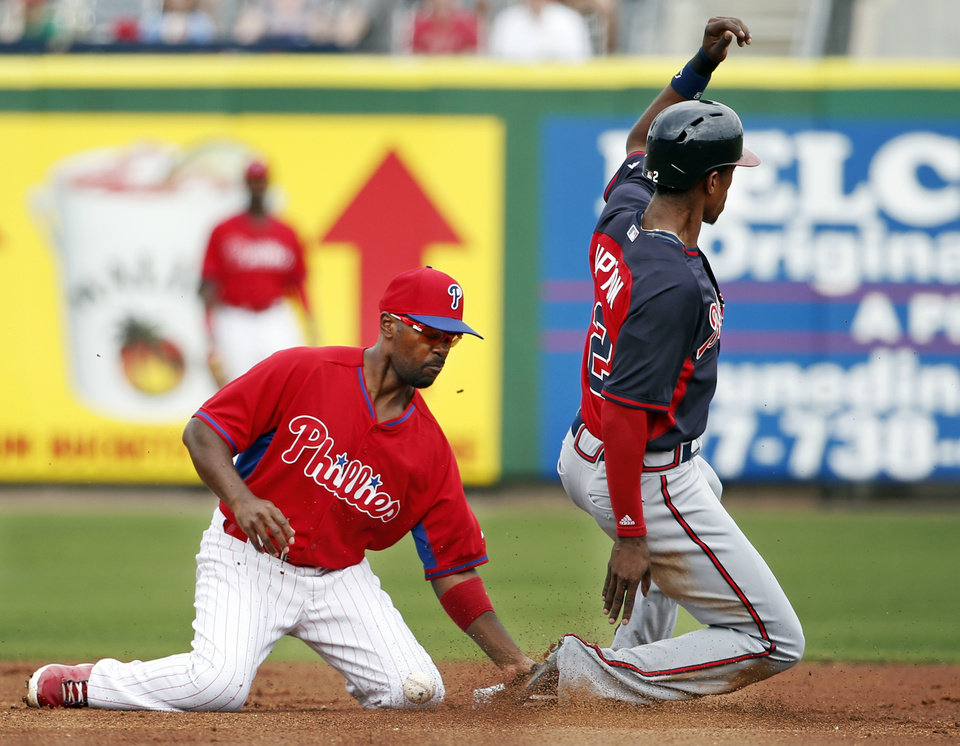 Photo - Atlanta Braves B.J. Upton, right, slides safely into second on a steal during the first inning as Philadelphia Phillies shortstop Jimmy Rollins bobbles the ball in a spring exhibition baseball game in Clearwater, Fla., Monday, March 10, 2014.  The Braves won 8-1. (AP Photo/Kathy Willens)