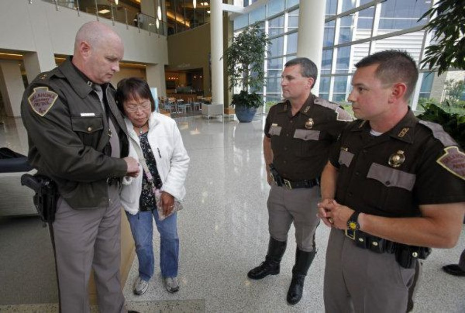 Nenita Mijares gets a hug from Capt. Chris West as she thanks Highway Patrol Troopers Steve Johnson (center) and Ken Pittman at the Norman Regional Healthplex on Thursday, April 21, 2011, in Norman, Okla.  The troopers performed CPR on her husband Hector Mijares, a retired commercial airline pilot, while working a multi-vehicle accident at Interstate 35 and 27th Street in Moore, OK.  The couple are living in Oklahoma City after retiring in the Philippines. Photo by Steve Sisney, The Oklahoman ORG XMIT: KOD