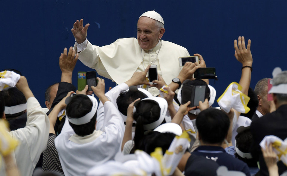 Photo - Pope Francis is greeted by the faithful upon his arrival for the Mass of Assumption of Mary at a stadium in Daejeon, south of Seoul, South Korea, Friday, Aug. 15, 2014. North Korea has Catholics. It even has a Catholic church. But while Pope Francis is being welcomed by millions of South Korean Catholics, Christianity has been largely quashed north of the border and as a string of recent arrests suggest would-be missionaries there face severe risks amid a North-South religious divide that is perhaps wider than ever. (AP Photo/Lee Jin-man, Pool)