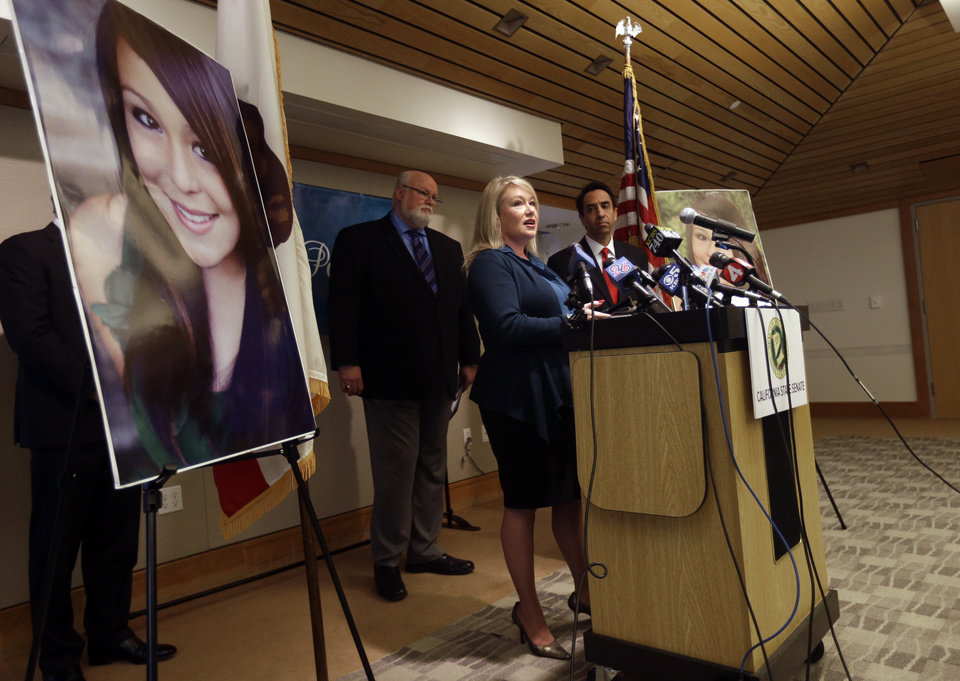 Photo - Sheila Pott, center, mother of Audrie Pott, reads a statement in support of Audrie's Law as State Sen. Jim Beall, D-San Jose, center, left, and Santa Clara County District Attorney Jeff Rosen, center right, listen in on Friday, March 7, 2014, in Saratoga, Calif. Audrie's Law is a legislative proposal aimed at deterring the bullying, cyberbullying, and sexual assault that played roles in the suicide of Audrie Pott, a 15-year-old Saratoga High School student. (AP Photo/Marcio Jose Sanchez)