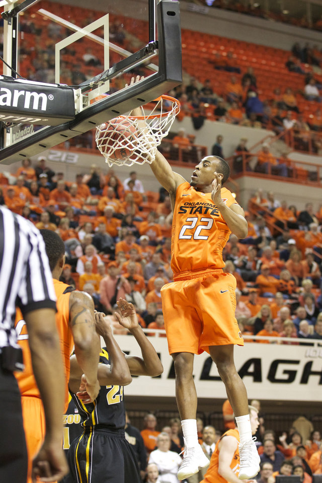 Photo - Markell Brown dunks over a Missouri defender during a game on Wednesday, Jan. 25, 2012. PHOTO COURTESY OSTATEPHOTO.COM  Bruce Waterfield