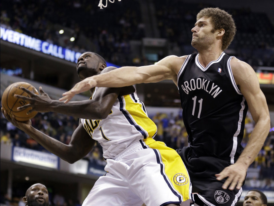 Brooklyn Nets center Brook Lopez, right, fouls Indiana Pacers guard Lance Stephenson as he shoots in the second  half of an NBA basketball game in Indianapolis, Monday, Feb. 11, 2013. The Nets defeated the Pacers 89-84 in overtime. (AP Photo/Michael Conroy)