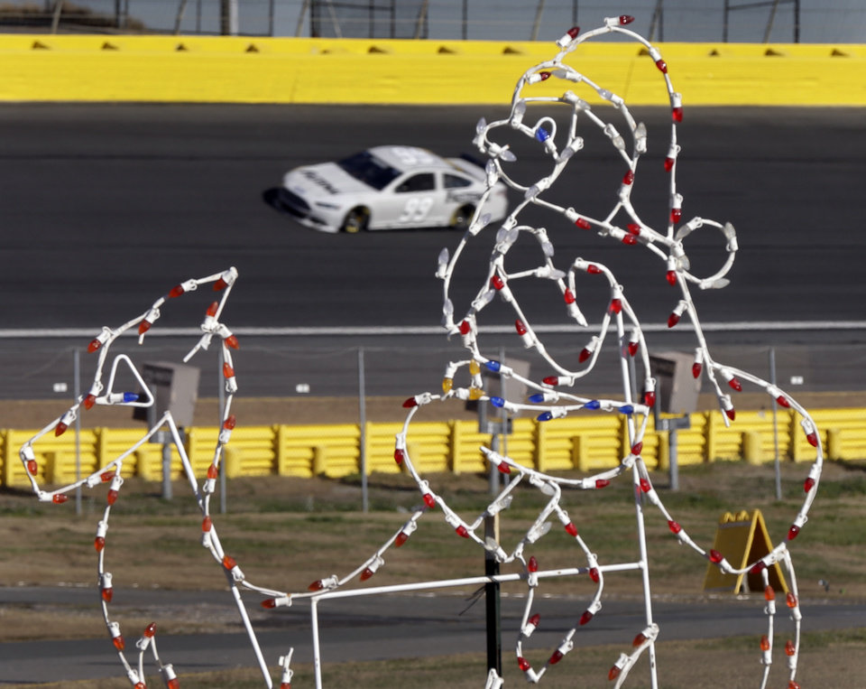 Photo - Carl Edwards takes his car through Turn 3 past a holiday light display during NASCAR Sprint Cup testing for the 2014 season at Charlotte Motor Speedway in Concord, N.C., Wednesday, Dec. 11, 2013. (AP Photo/Chuck Burton)